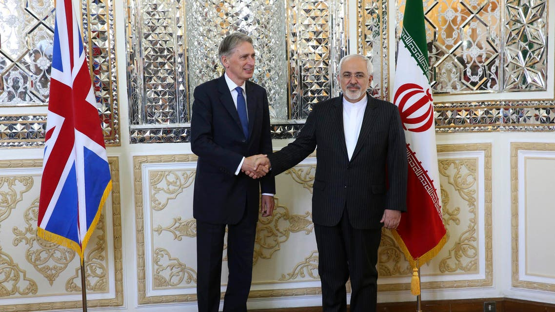 Iranian Foreign Minister Mohammad Javad Zarif, right, and British Foreign Secretary Philip Hammond, shake hands for media prior to their meeting in Tehran, Iran, Sunday, Aug. 23, 2015. British Foreign Secretary Philip Hammond reopened the British Embassy in Tehran on Sunday, nearly four years after it was closed following an attack by hard-liners. (AP Photo/Vahid Salemi)