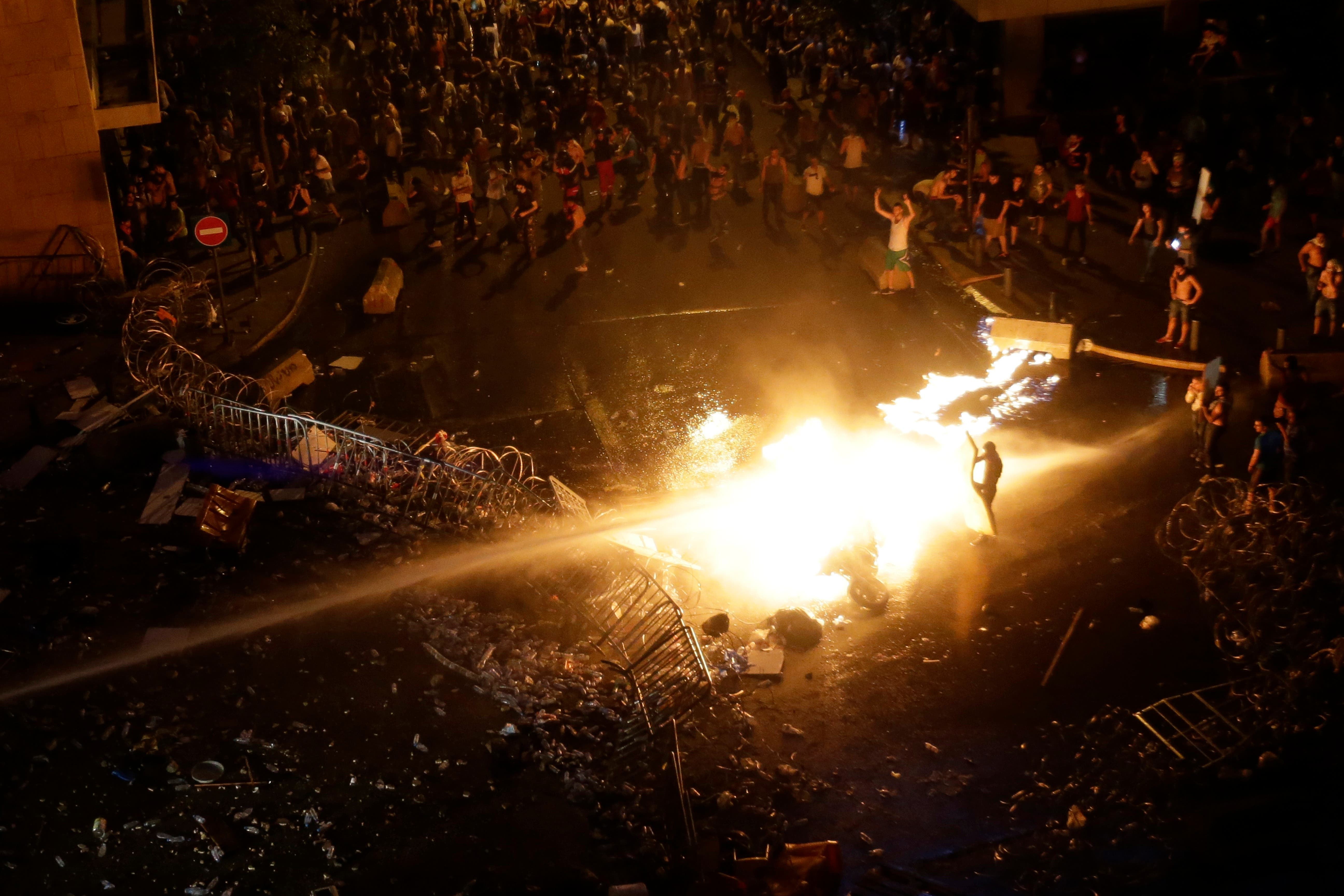 Lebanese protesters set a police motorcycle on fire as they are sprayed by riot police using water cannons during a protest against the ongoing trash crisis, in downtown Beirut, Lebanon, Sunday, Aug. 23, 2015.  (AP)