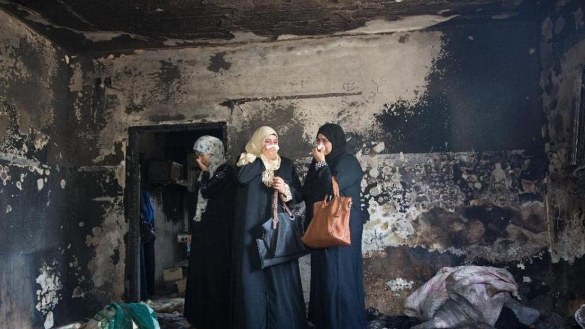 Palestinian women look at the damage at the Dawabsha family's home in the West Bank village of Duma on August 4, 2015, after it was set on fire by Jewish extremists (AFP Photo/Menahem Kahana)