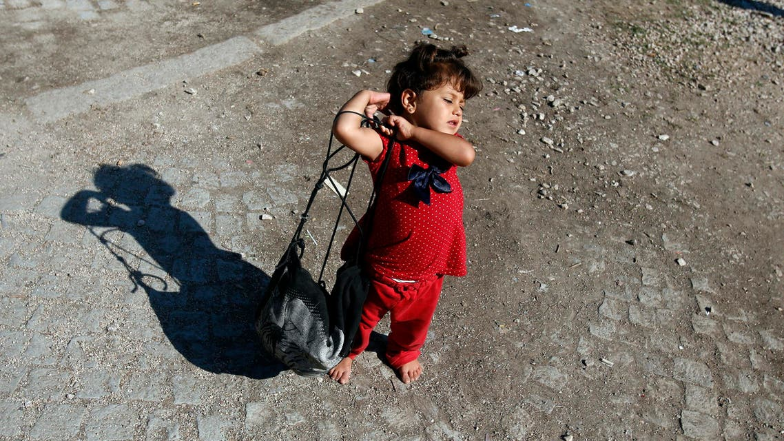 A migrant girl carries her bag at a migrant processing center in the southern Serbian town of Presevo, Monday, Aug. 24, 2015. (AP)