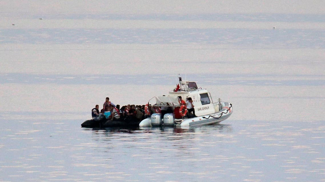 Turkish Coast Guard officers on a boat capture migrants from the coastal town of Bodrum, Turkey, headed to the Greek island of Kos, on Saturday, Aug. 15, 2015. AP