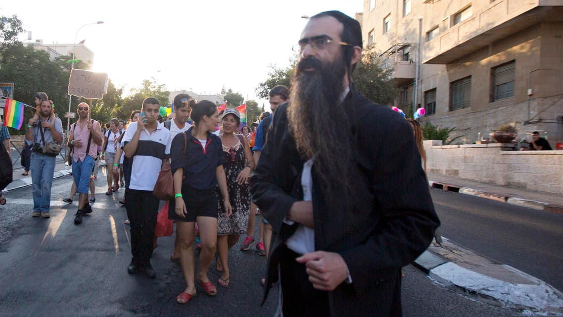 Ultra-Orthodox Jew Yishai Schlissel walks through a Gay Pride parade and is just about to pull a knife from under his coat and start stabbing people in Occupied Jerusalem. (File: AP)