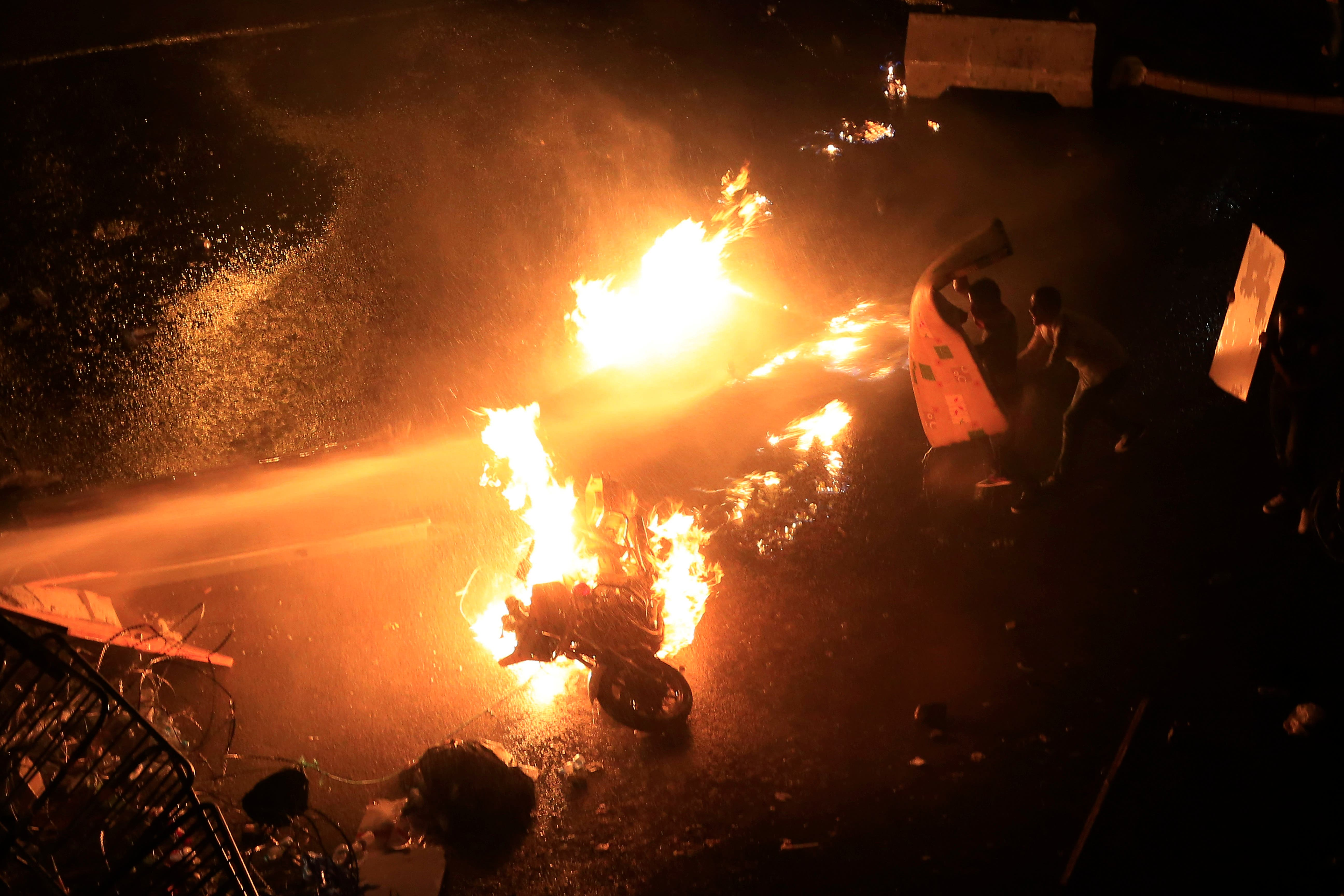 A police motorcycle burns as Lebanese protestors are sprayed by riot police using water cannons, during a protest against the ongoing trash crisis, in downtown Beirut, Lebanon, Sunday, Aug. 23, 2015. AP