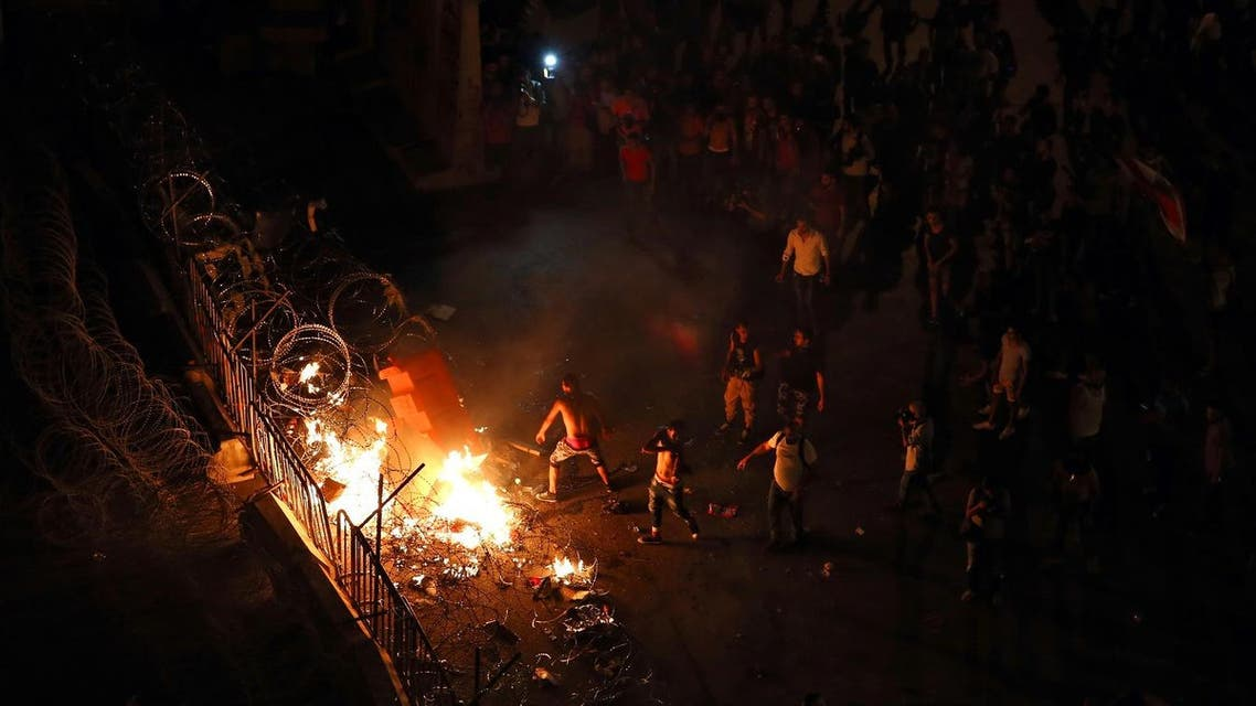 Lebanese activists set fire to plastic barriers and trash behind the barbed wire separating them from the police, during a protest against the ongoing trash crisis, in downtown Beirut. (AP)