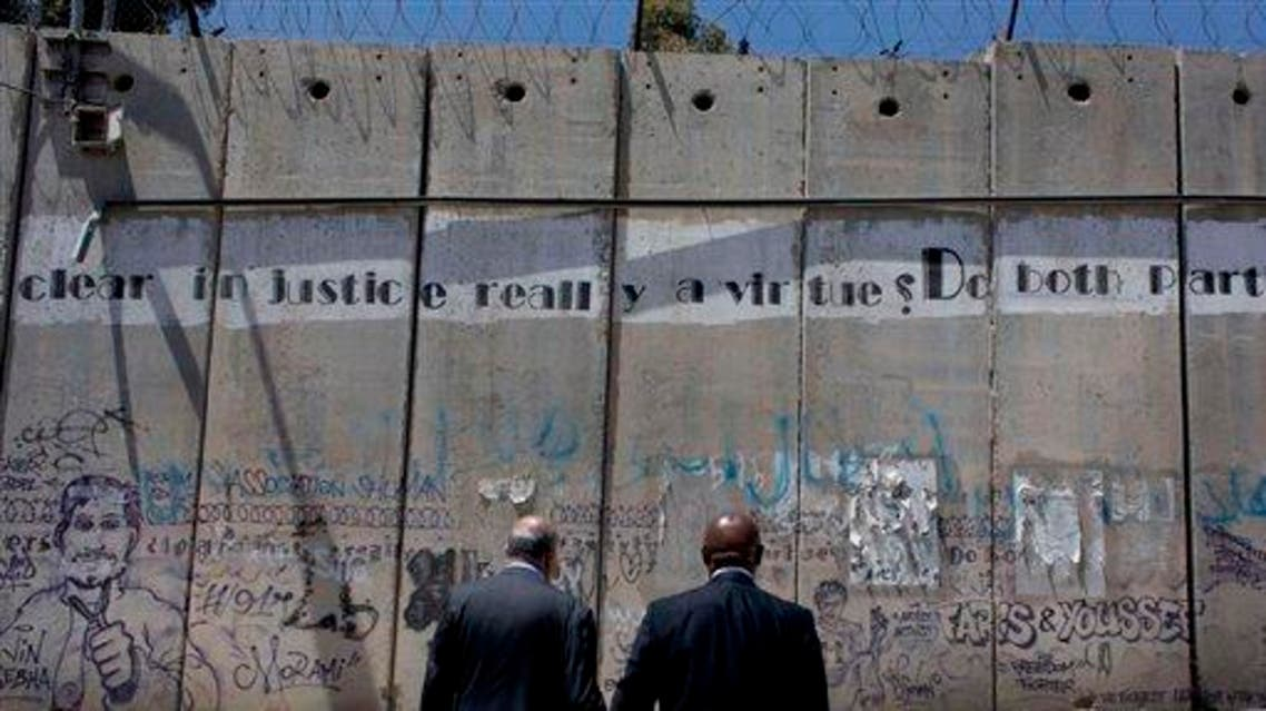 President of the anti-racism campaign Global Watch, Tokyo Sexwale, right, and head of Palestinian Football Association, PFA, Jibril Rajoub inspect the separation barrier on the outskirts of the West Bank city of Ramallah, Thursday, May 7, 2015. FIFA says it will host the leaders of the Israeli and Palestinian soccer federations within days, seeking an agreement before the governing body's congress this month. The Palestinian Football Association wants Israel suspended from world soccer because its security forces restrict movement of players in the West Bank and Gaza. (AP Photo/Nasser Nasser)