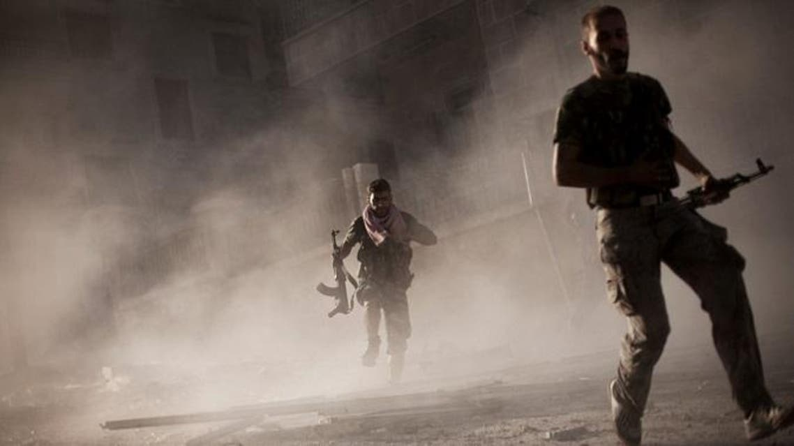 free Syrian Army fighters run after attacking a Syrian Army tank during fighting in the Izaa district in Aleppo, Syria, September 7, 2012. (AP)