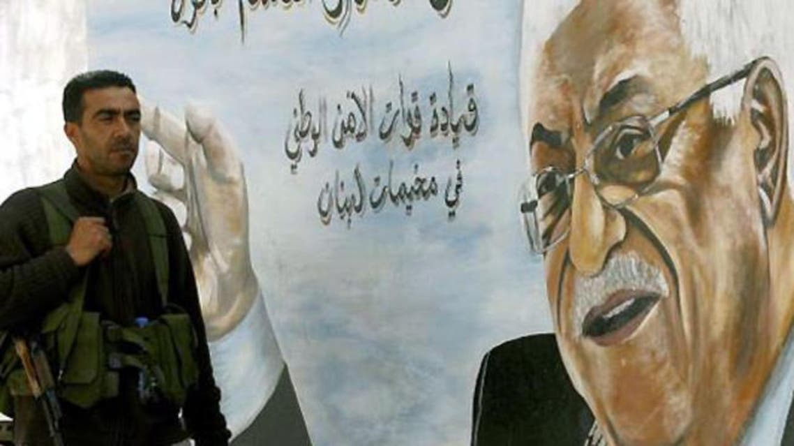 A Fatah movement member stands next to a mural of the Palestinian leader Mahmud Abbas in the Ain al-Hilweh Palestinian refugee camp on the outskirts of the southern Lebanese city of Sidon. (AFP/File)