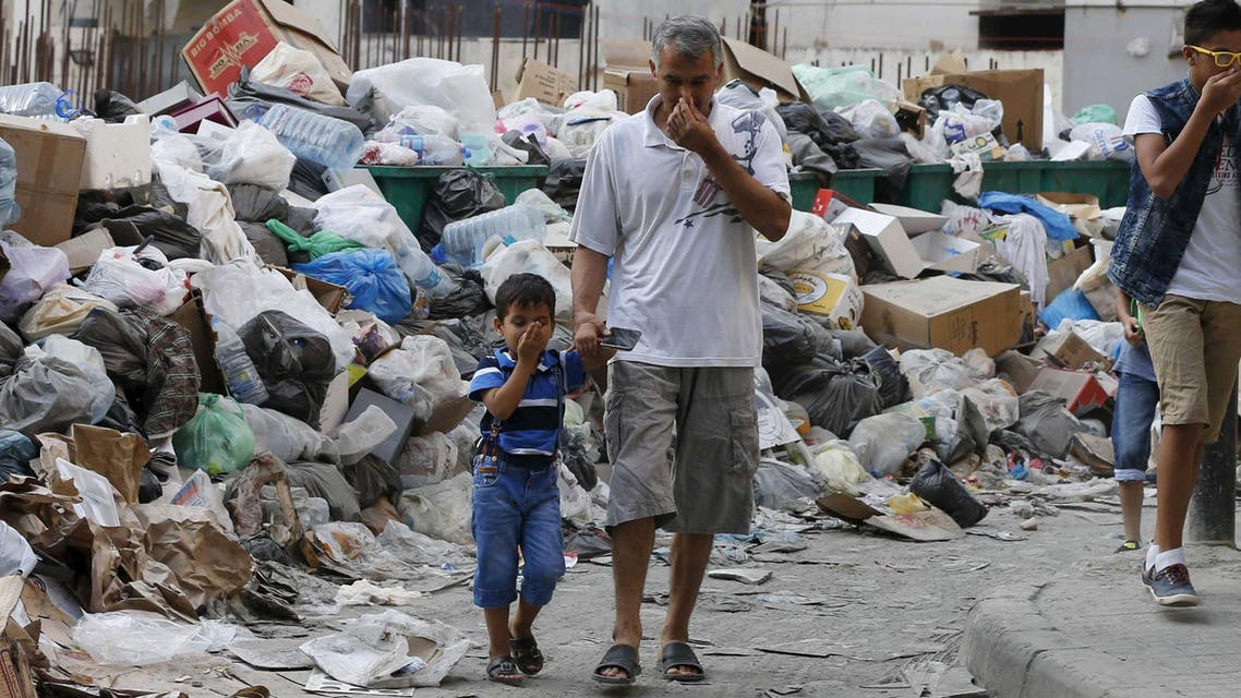 Residents cover their noses as they walk past garbage piled up along a street in Beirut, Lebanon August 26, 2015. (Reuters)