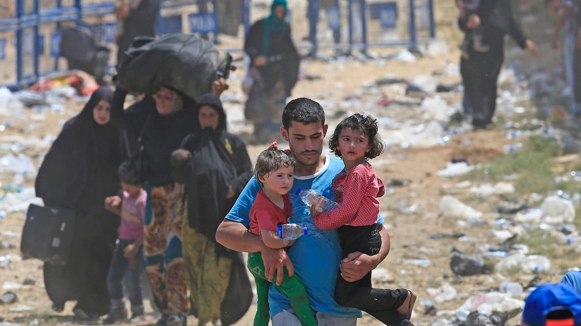A Syrian refugee carrying children, walks in Turkey, in Akcakale, southeastern Turkey, as he and others flee intense fighting in northern Syria between Kurdish fighters and Islamic State militants, Monday, June 15, 2015. AP