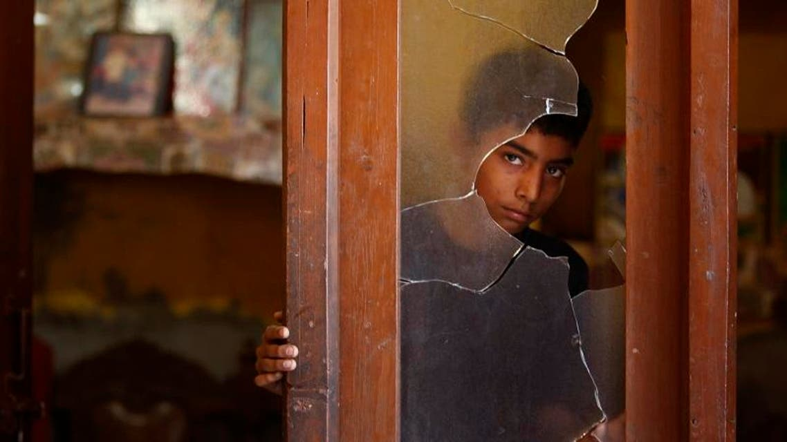 An Indian boy looks outside a glass window damaged in alleged firing from the Pakistan side into a residential area at Sai village, in Ranbir Singh Pura near the India-Pakistan international border. (AP)