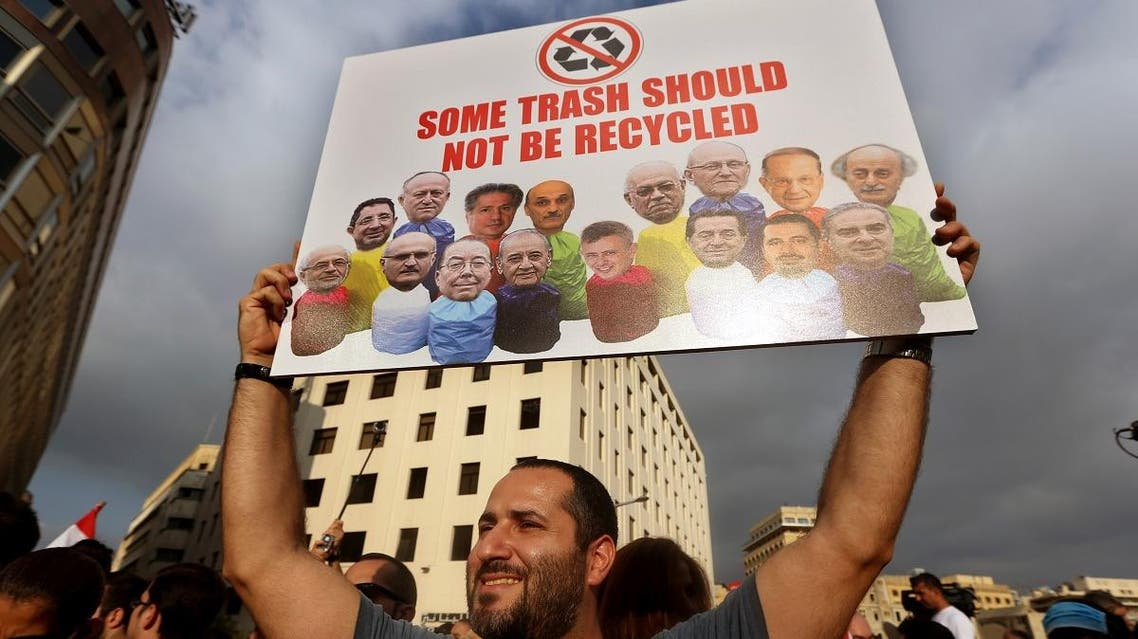 In this August 22, file photo, a Lebanese activist holds a poster with pictures of Lebanese Cabinet ministers during a protest against the ongoing trash crisis, in downtown Beirut. (AP)