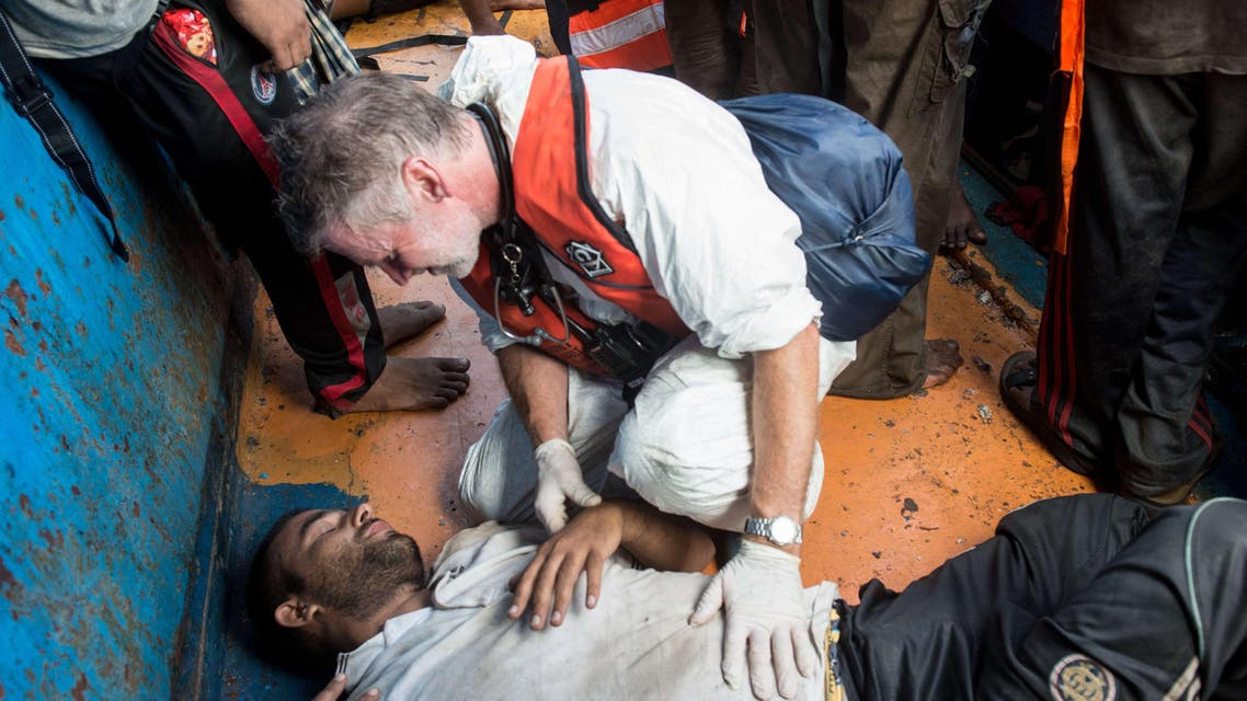 "ITA12505 - -, MEDITERRANEAN SEA, - : In this handout picture released by the French NGO Medecins Sans Frontières (Doctors without borders - MSF) on August 27, 2015 a doctor gives medical assistance to a migrant in a wooden boat during a rescue operation by MSF and the Swedish Coast Guards ""Poseidon"" in the Meditterranean sea. At least 55 dead bodies were discovered during this operation on August 26, 2015 on three overcrowded migrant boats in the Mediterranean, the Italian coastguard said. Almost all of the victims -- 51 -- were found in the hold of a wooden boat found drifting precariously off the Libyan coast by Swedish coastguard vessel the Poseidon. Media reports said they had choked to death on gas fumes from the small motor boat. AFP PHOTO / GABRIELE FRANCOIS CASINI / MEDECINS SANS FRONTIERES"