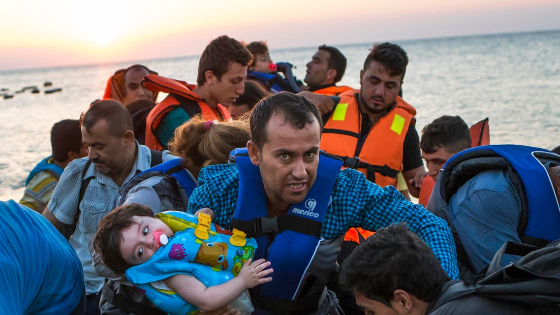 A man carries a girl in his arm as migrants arrive at a coast on a dinghy after crossing from Turkey in the southeastern island of Kos, Greece, during the sunrise early Thursday, Aug. 13, 2015 AP