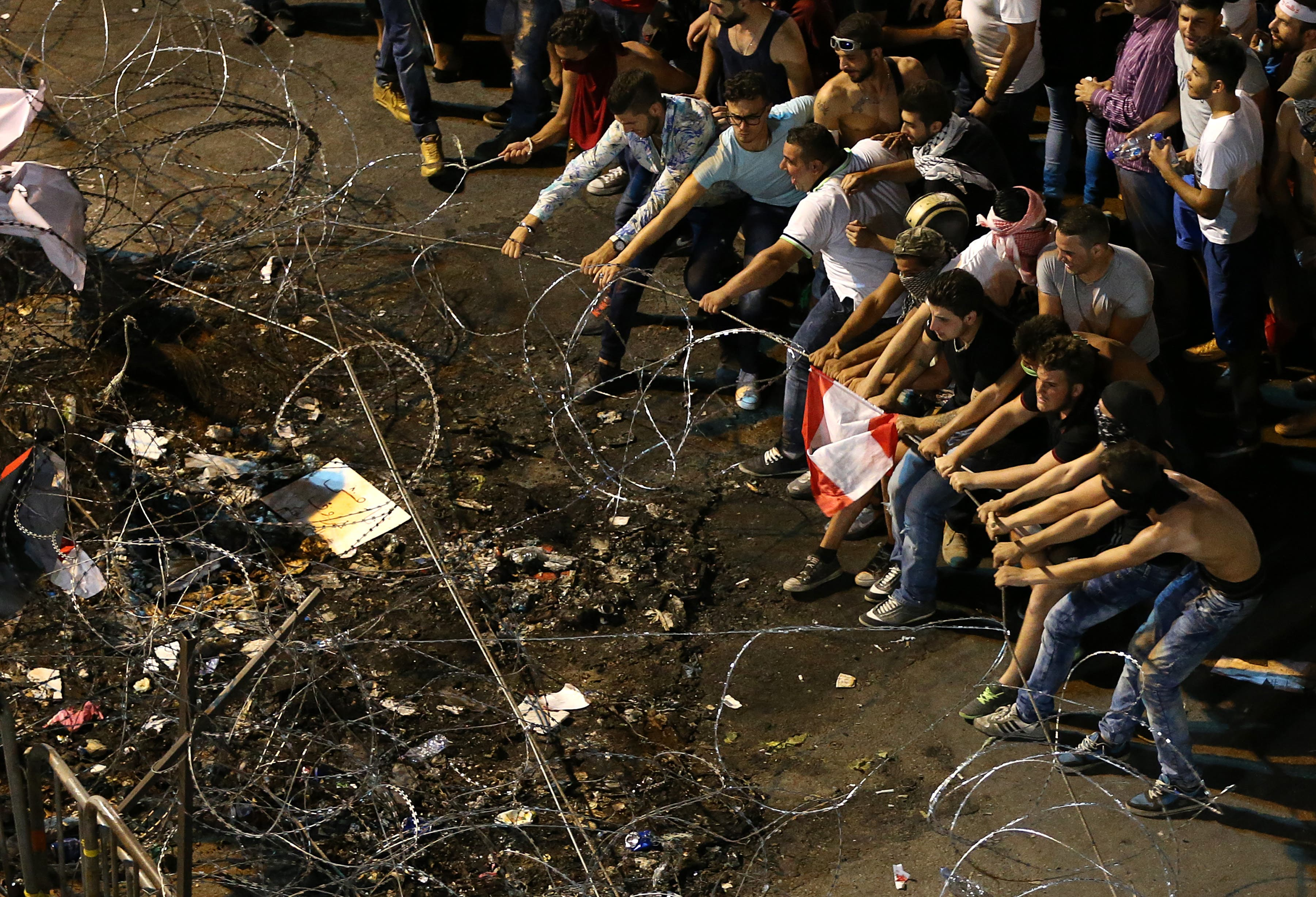 Lebanese anti-government protesters try to remove barbed wire that blocks the road to the government building, during a demonstration in downtown Beirut, Lebanon, Saturday, Aug. 29, 2015.  (AP)