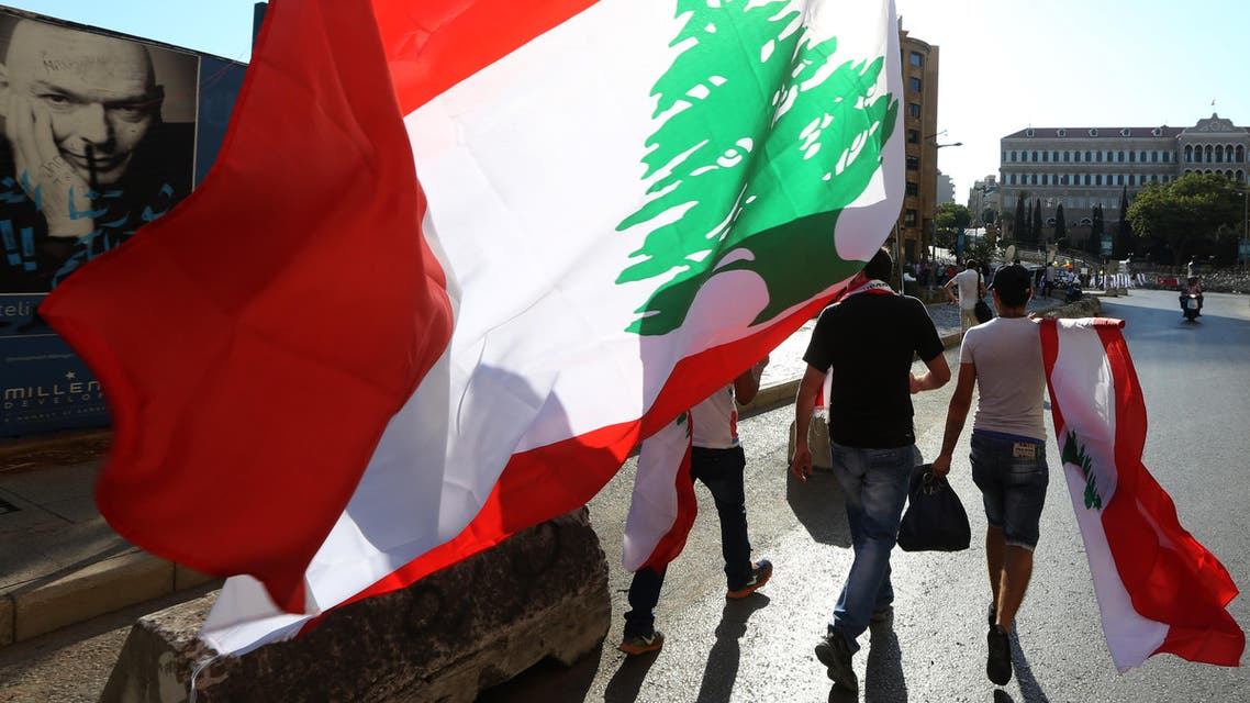 Lebanese anti-government protesters carry Lebanese flags as they walk towards the government building, background, during a demonstration against the trash crisis and government corruption, in downtown Beirut, Lebanon, Saturday, Aug. 29, 2015. (AP)