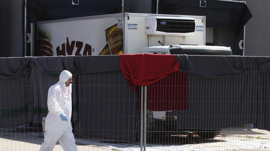 A member of a forensic team walks in front of a truck in which more than 70 bodies were found, at a customs building with refrigeration facilities in the village of Nickelsdorf. (File: Reuters)