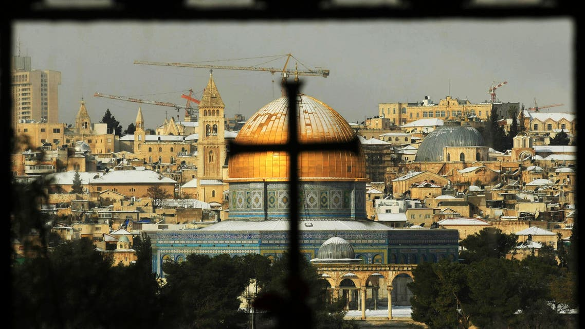 The Dome of the Rock Mosque is seen covered with snow through the window of the Church of Dominus Flevit outside Jerusalem's Old City, Thursday, Jan. 31, 2008. AP