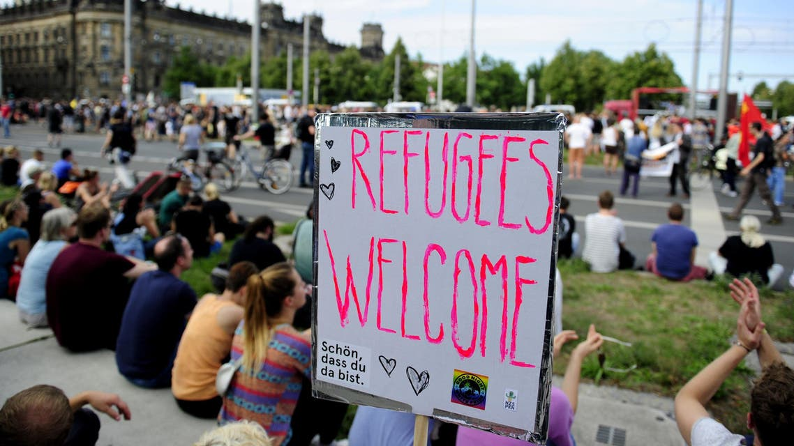 """An anti-racism protesters sit behind a banner with the lettering """"Refugees Welcome"""" during a rally on August 29, 2015 in Dresden, Germany. (AFP)"""