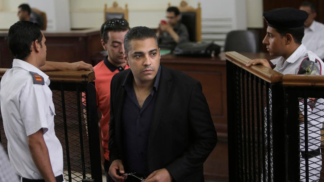 n this Thursday, June 25, 2015 file photo, policemen accompany Canadian Al-Jazeera English journalist Mohammed Fahmy during his retrial at a courtroom in Tora prison in Cairo, Egypt. AP