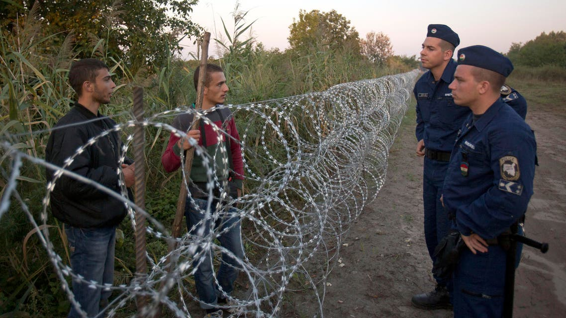 Syrian refugees and Hungarian police chat at the barbed wire fence at the border between Serbia and Hungary, in Roszke, Hungary Friday, Aug. 28, 2015. Hungary deployed police reinforcements to rein in an unrelenting flow of migrants across its porous border Thursday, but refugee activists said the effort appeared futile in a nation whose migrant camps are overloaded and barely delay their journeys west into the heart of the European Union. (AP Photo/Darko Bandic)