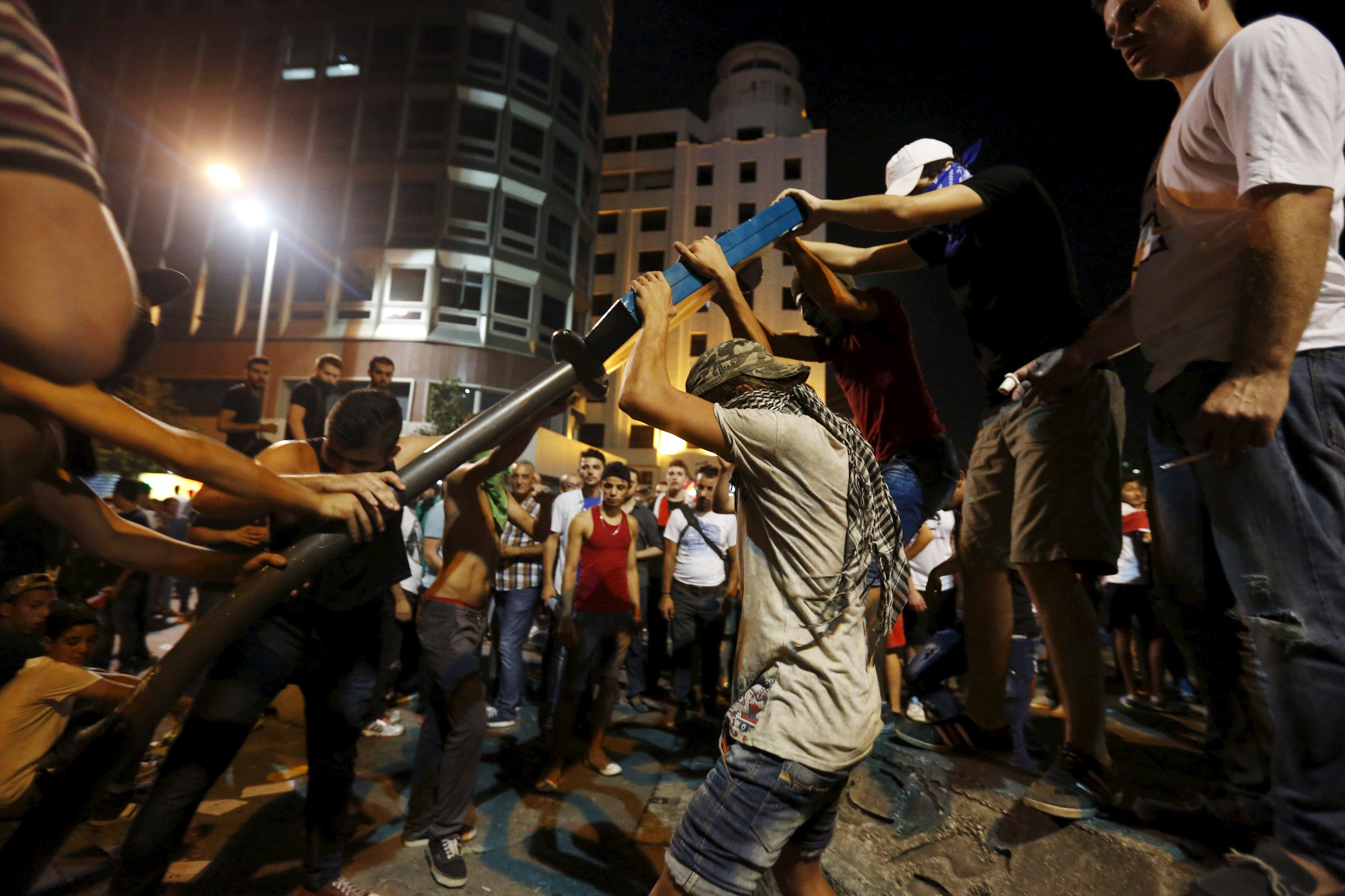 Protesters attempt to break a street sign near the government palace in downtown Beirut, Lebanon August 29, 2015. (Reuters)
