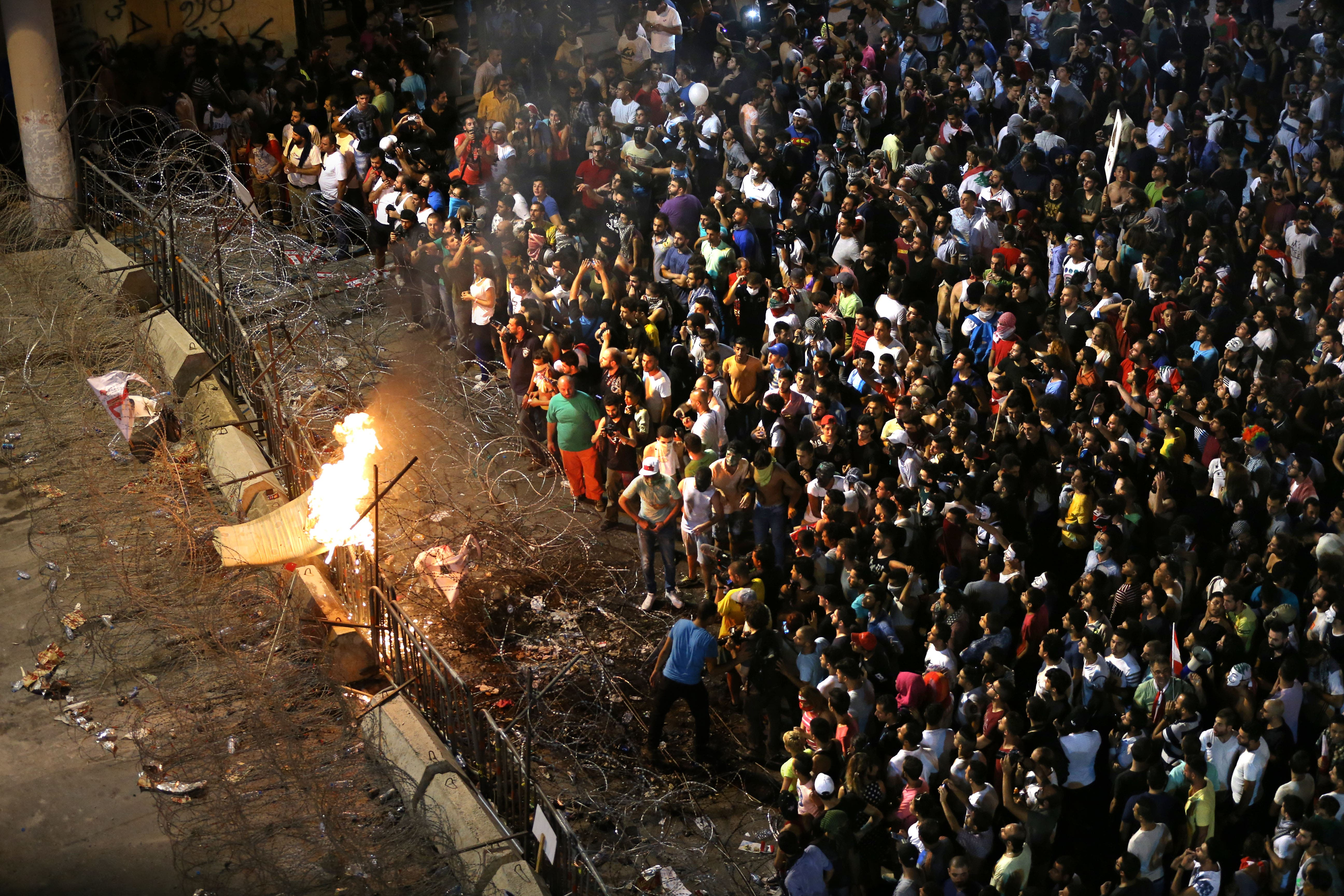 Lebanese anti-government protesters burn a mattress on a barbed wire barrier that blocks the road to the government building, during a demonstration in downtown Beirut, Lebanon, Saturday, Aug. 29, 2015.  (AP)