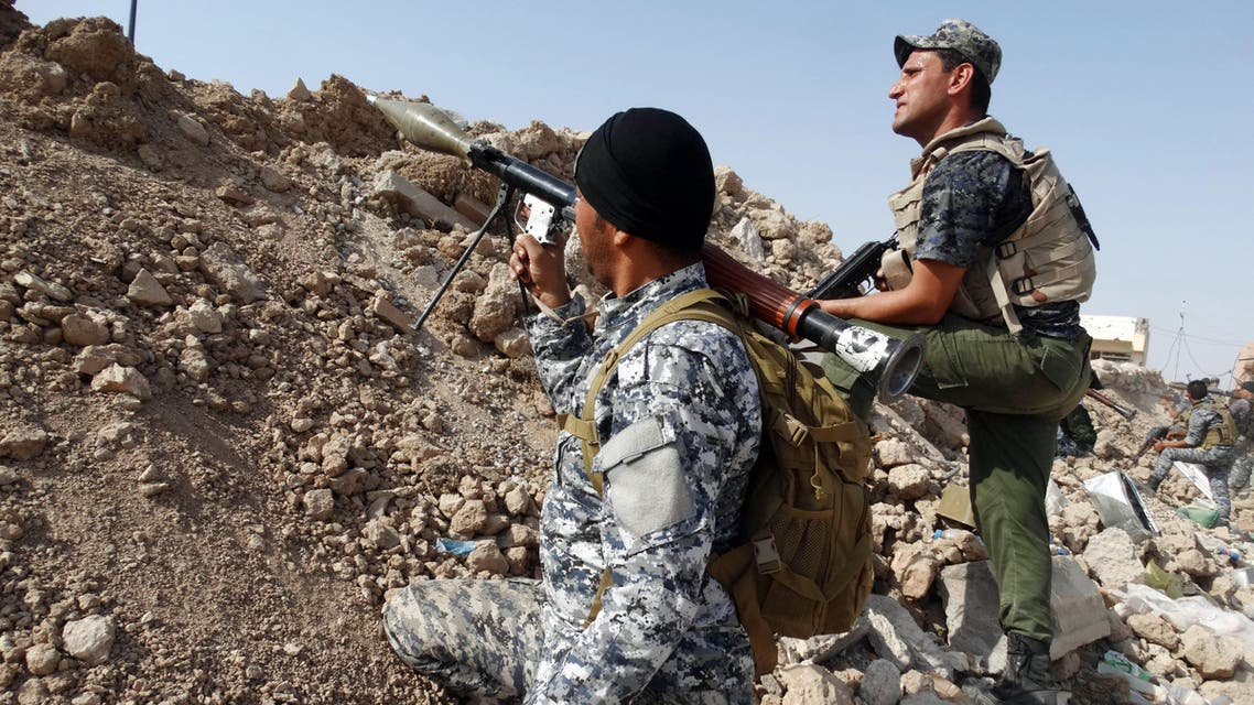 In this Thursday, Aug. 27, 2015 photo, Iraqi security forces, backed by Sunni and Shiite volunteers take combat positions during clashes with Islamic State group militants at the front line in Anbar province, Iraq. (AP Photo)