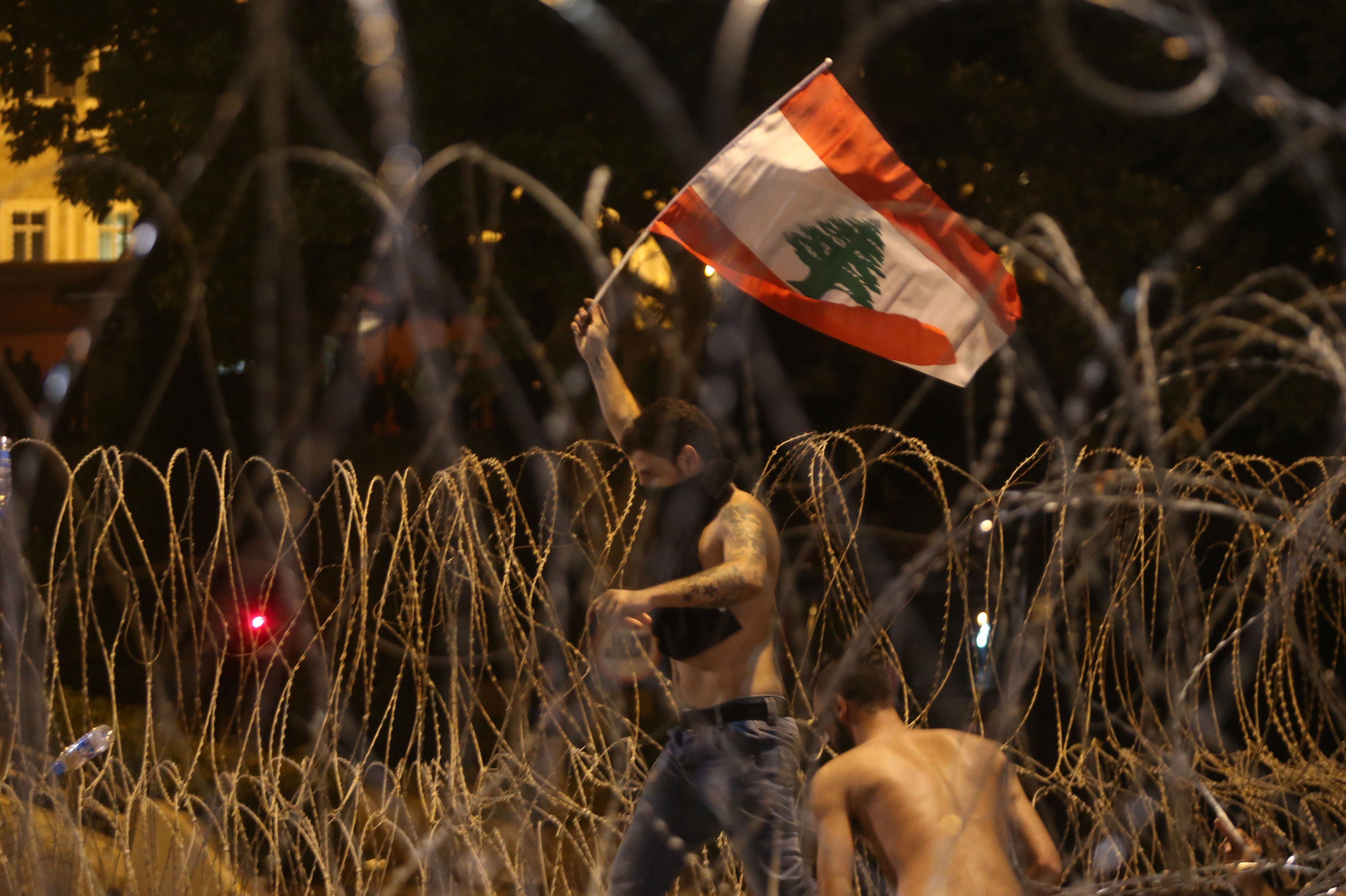 A Lebanese man waves a national flag as he tries to cross the barbed wire separating the protesters from the governmental palace on August 29, 2015. (AFP)