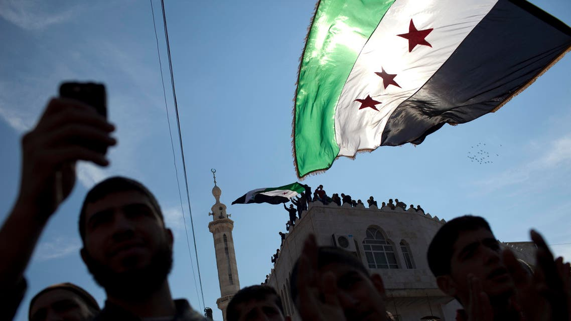 In this Friday, March 2, 2012 file photo, men hold revolutionary Syrian flags during an anti-government protest in a town in northern Syria. AP
