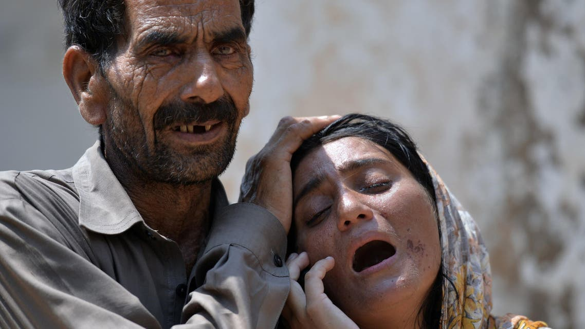 AQ7121 - Kundanpur, -, PAKISTAN : Pakistani woman, Laila (R) is comforted as she mourns the killing of her husband following the cross-border shelling by the Indian Border Security Force (BSF), in Kundanpur on the India-Pakistan border near the eastern city of Sialkot on August 29, 2015. At least 10 civilians were as India and Pakistan traded fire across their disputed border, officials said, less than a week after high-level talks were aborted amid a row over Kashmir. AFP PHOTO / Aamir QURESHI