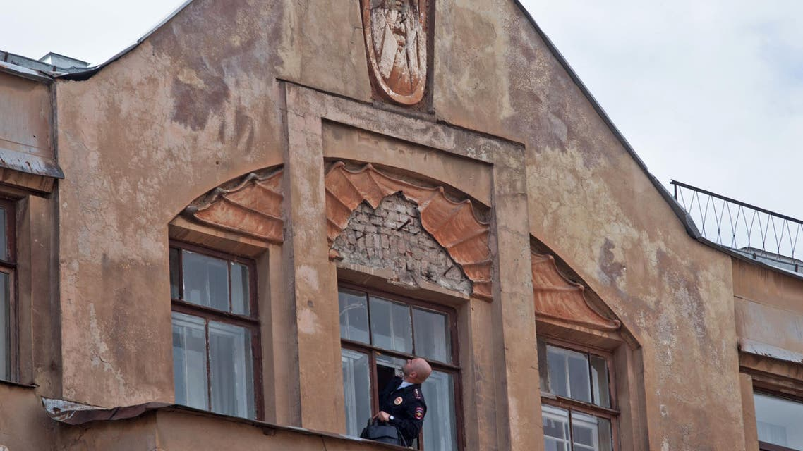 A police investigator looks up to at an empty spot where an old bas relief depicting the mythical demon Mephistopheles was removed in St. Petersburg, Russia, Friday, Aug. 28, 2015. (AP)