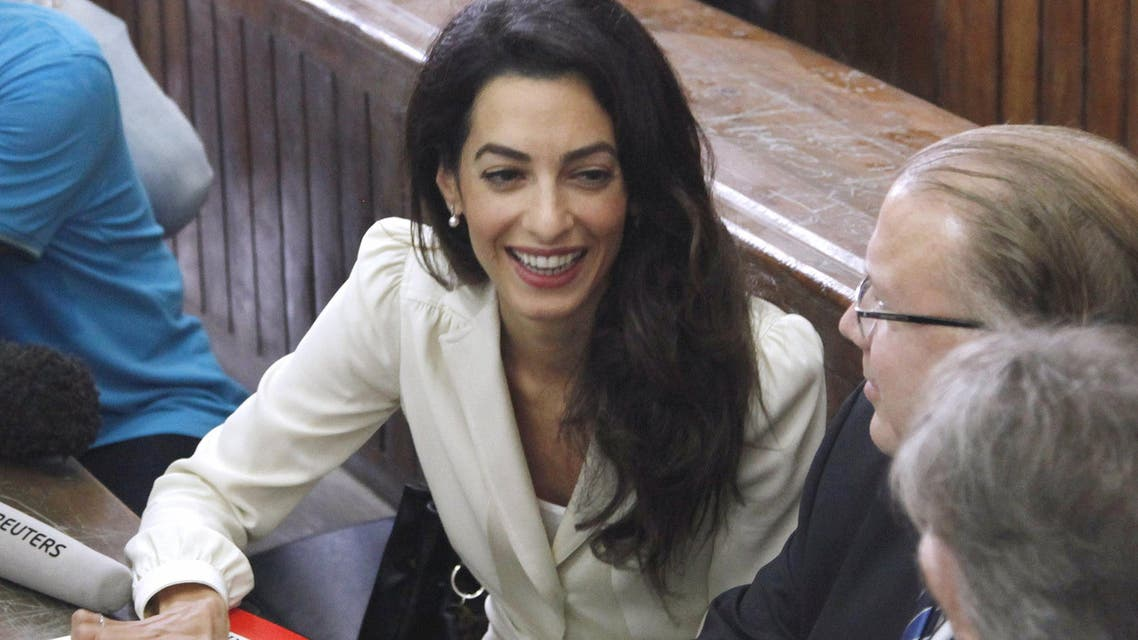 Lawyer Amal Clooney, defending Al Jazeera television journalist's Mohamed Fahmy, talks to Troy Lulashnyk, Canadian Ambassador to Egypt, before hearing the verdict at a court in Cairo, Egypt, August 29, 2015. (Reuters)