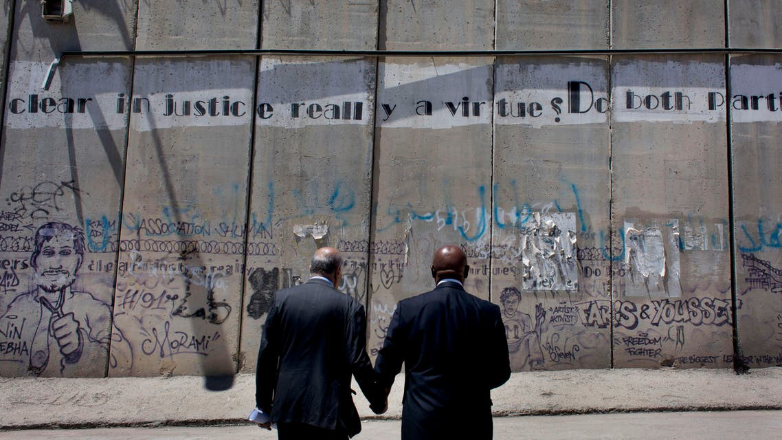 President of the anti-racism campaign Global Watch, Tokyo Sexwale, right, and head of Palestinian Football Association, PFA, Jibril Rajoub inspect the separation barrier on the outskirts of the West Bank city of Ramallah, Thursday, May 7, 2015. AP