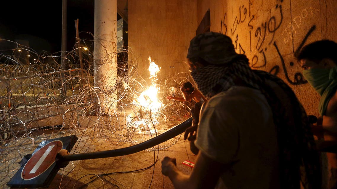 Protesters carry a broken street sign as they set trash on fire on barbed wire erected near the government palace in downtown Beirut, Lebanon August 29, 2015.