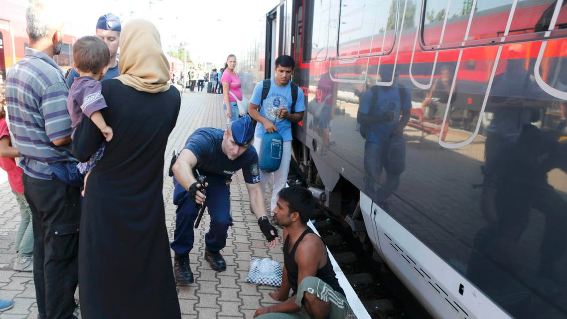 A Hungarian police officer gestures to a traveller as a train heading for Austria, with migrants on board, is stopped for checks at a border station in Hegyeshalom, Hungary, August 31, 2015. Austrian authorities toughened controls along the country's eastern borders on Monday, stopping hundreds of refugees and arresting five traffickers in a clampdown that followed last week's gruesome discovery of 71 dead migrants in a truck. REUTERS/Heinz-Peter Bader