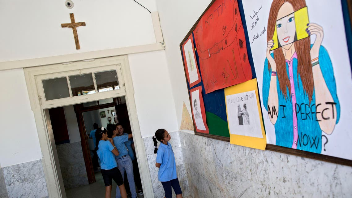 In this photo taken Tuesday, May 26, 2015, An Arab Israeli Christian school girl looks at a board with drawings at the Terra Santa School in the mixed Jewish-Arab city of Ramle, Israel. Private Christian schools are among Israel's highest ranked educational institutions, established by churches in the Holy Land hundreds of years ago long before Israel was established. But school administrators are accusing Israel of slashing their funding as a pressure tactic to get them join the Israeli public school system a move they say would interfere with the schools' Christian values and high academic achievements. (AP Photo/Oded Balilty)