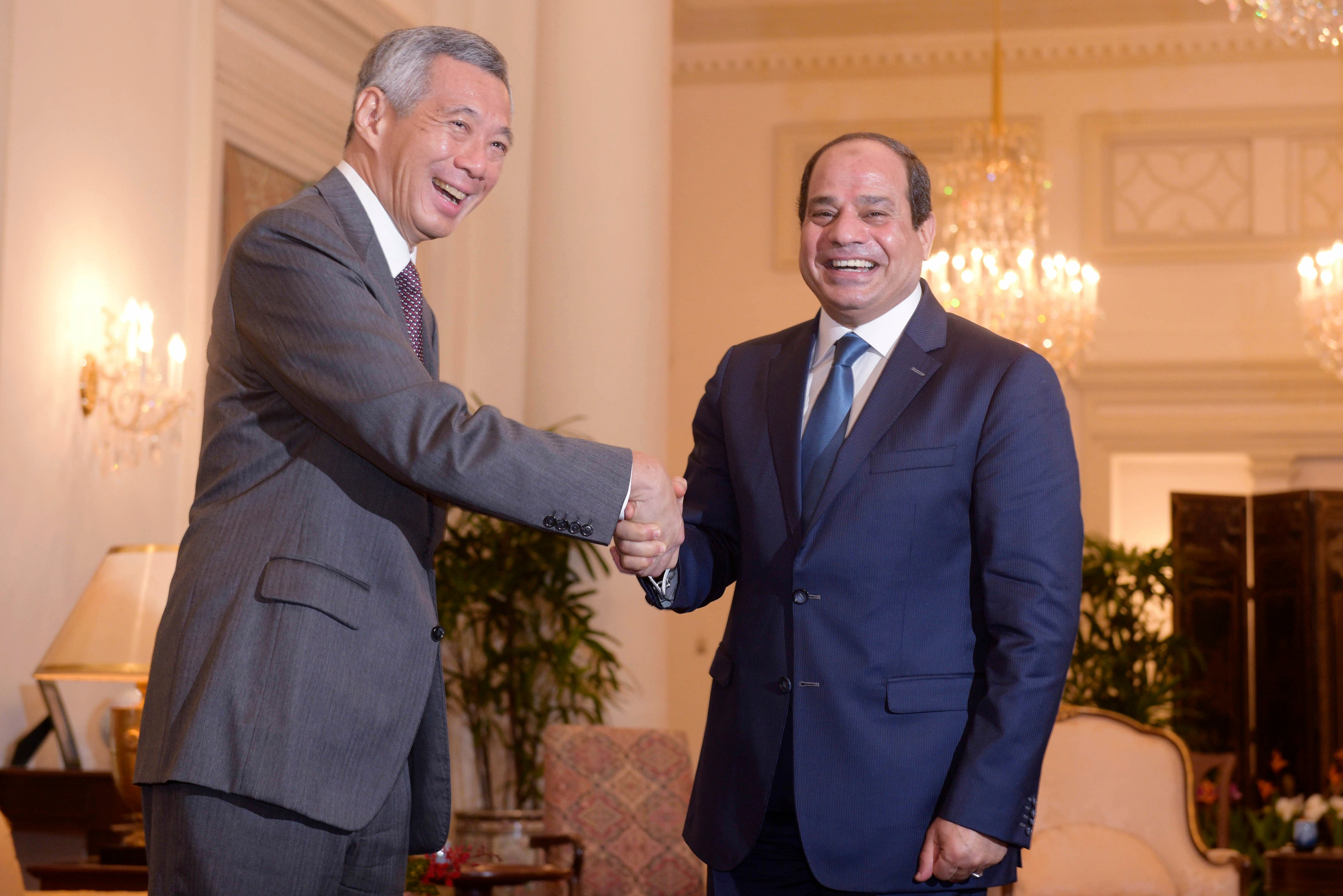 Singapore Prime Minister Lee Hsien Loong, left, greets Egyptian President Abdel-Fattah el-Sissi, right, at the Istana, or Presidential Palace, Monday, Aug. 31, 2015 in Singapore. (AP)