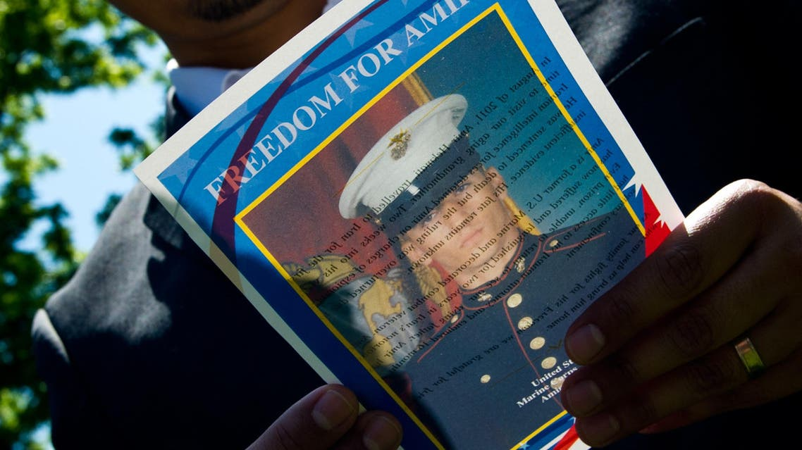 """This May 19, 2014 file photo shows a man as he reads a flyer with a photo of US Marine veteran Amir Hekmati during a vigil held in Lafayette Park across from the White House in Washington, DC. US Secretary of State John Kerry on August 28, 2015 urged Iran to free Amir Hekmati, an American who served as a US Marine, from four years of """"unjust detention."""" August 29, 2015 marks the fourth anniversary of Hekmati's imprisonment on what Kerry called """"false espionage charges"""" while Hekmati was visiting relatives in the Islamic republic. """"We repeat our call on the Iranian government to release Amir on humanitarian grounds,"""" Kerry said in a statement.""""This is a milestone no family wants to mark, and the Hekmati family has shown inspiring perseverance in the face of this injustice,"""" he added. AFP PHOTO / Karen BLEIER"""