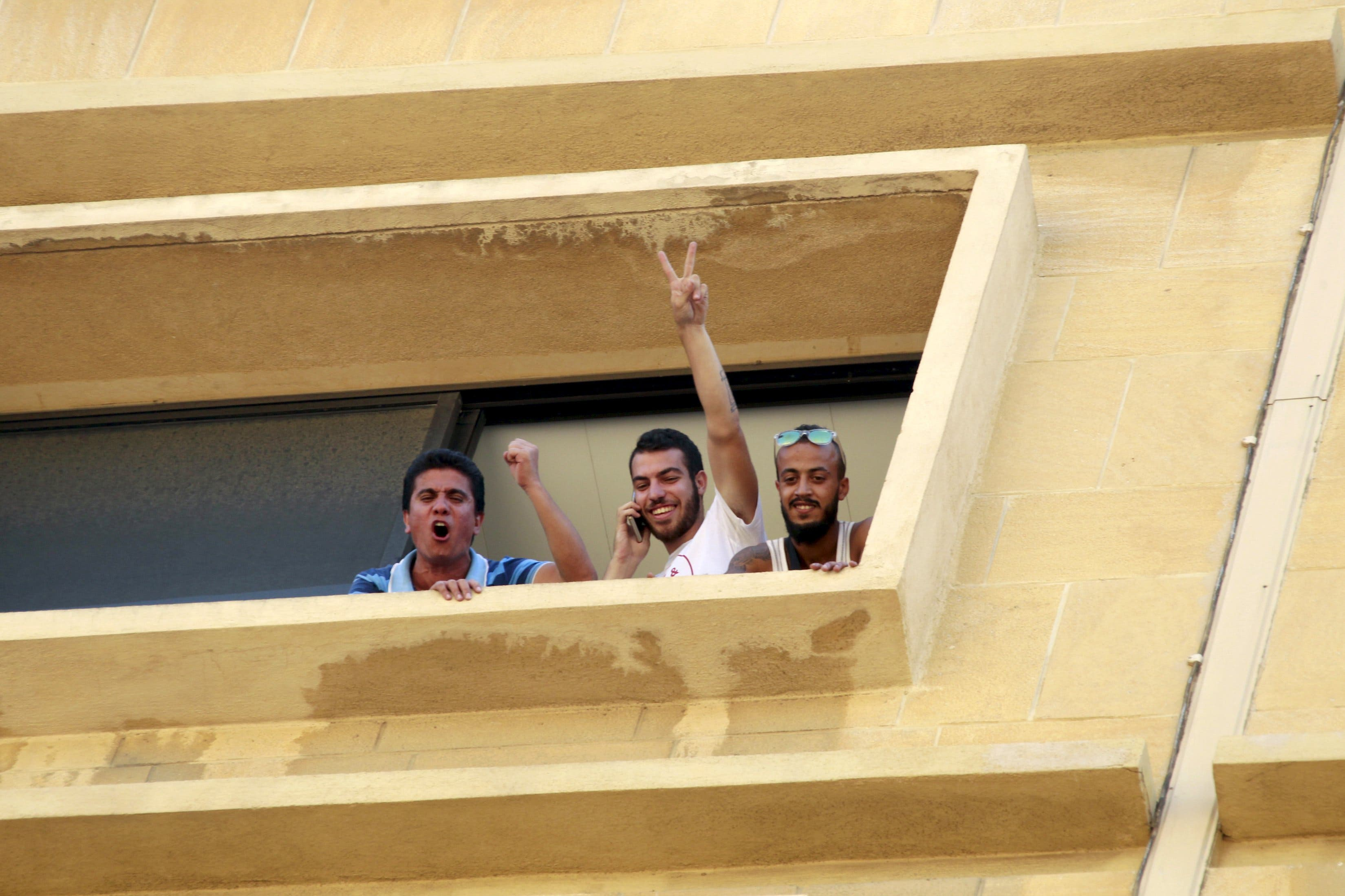 Protestors gesture from a window of the environment ministry in downtown Beirut, Lebanon September 1, 2015. Reuters