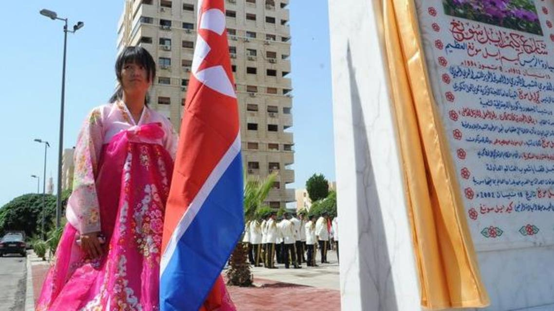 woman holds a North Korean flag during the inauguration ceremony of a park in the Syrian capital Damascus to honor North Korea's founding father Kim Il Sung. (AFP)