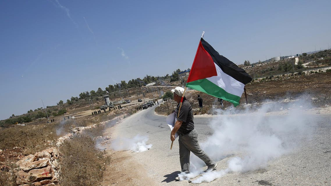 A Palestinian protester holds a Palestinian flag as he walks next to a tear gas canister fired by Israeli troops during clashes at a protest in solidarity with Palestinian detainee Mohammed Allan, in the West Bank village of Nabi Saleh, near Ramallah August 14, 2015. Reuters