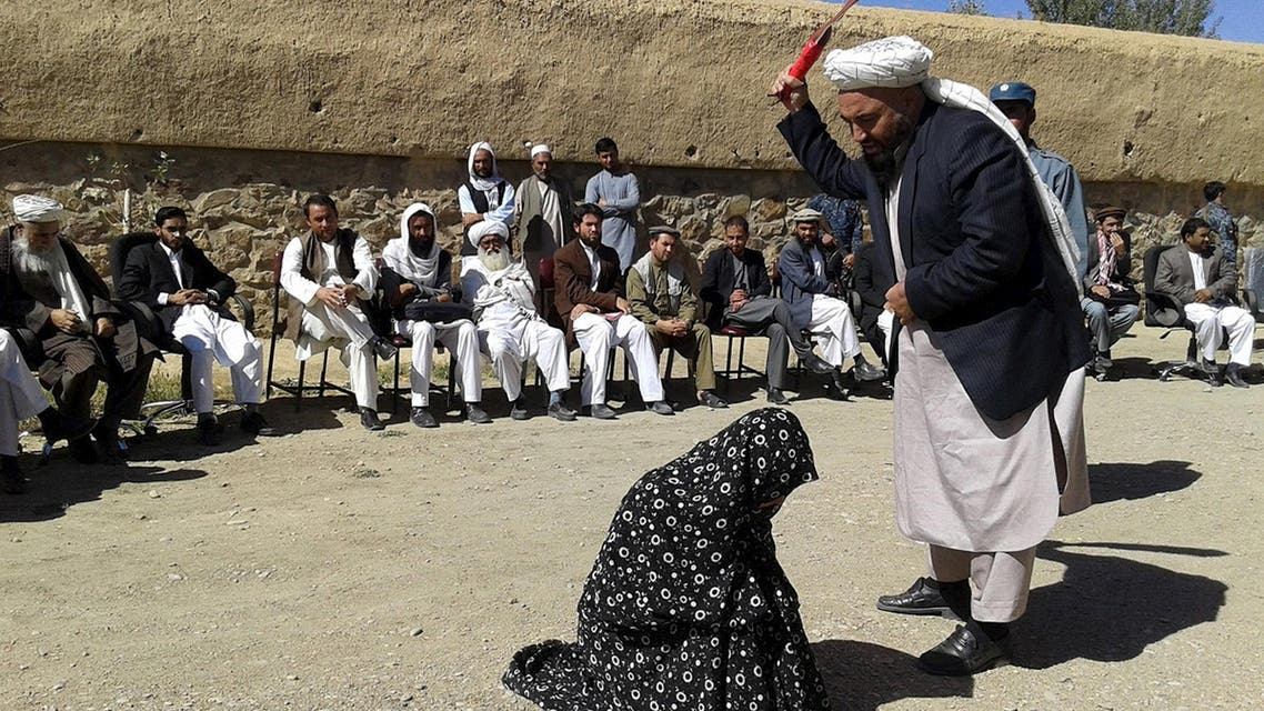 An Afghan judge hits a woman with a whip in front of a crowd in Ghor province, Afghanistan August 31, 2015. (Reuters)