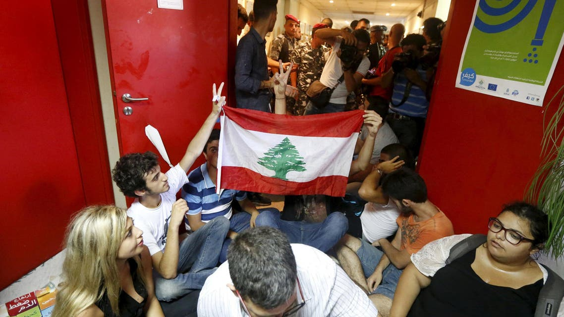 Protestors carry a Lebanese flag inside the environment ministry in downtown Beirut, Lebanon September 1, 2015. REUTERS
