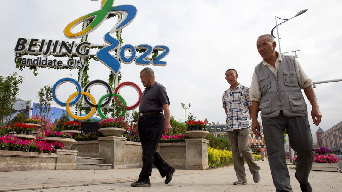 Chinese men walk past the Beijing 2022 Olympic bid logo in the mountain town of Chongli which will host the 2022 Nordic skiing, ski jumping, and other outdoor Winter Olympic events in northern China's Hebei province on Saturday, Aug. 1, 2015. Having made history as the first city to win hosting rights for both the Summer and Winter Olympics, Beijing now faces a slew of challenges, from ensuring adequate snow in a bone-dry region to ramping up support for winter sports in a nation where few people ski or skate. (AP Photo/Ng Han Guan)