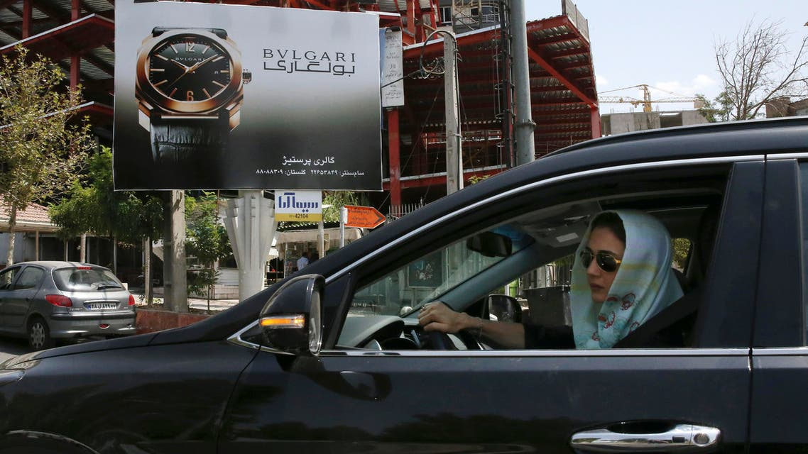 A woman drives in front of an advertising billboard in northern Tehran, Iran, Saturday, July 18, 2015. (AP)