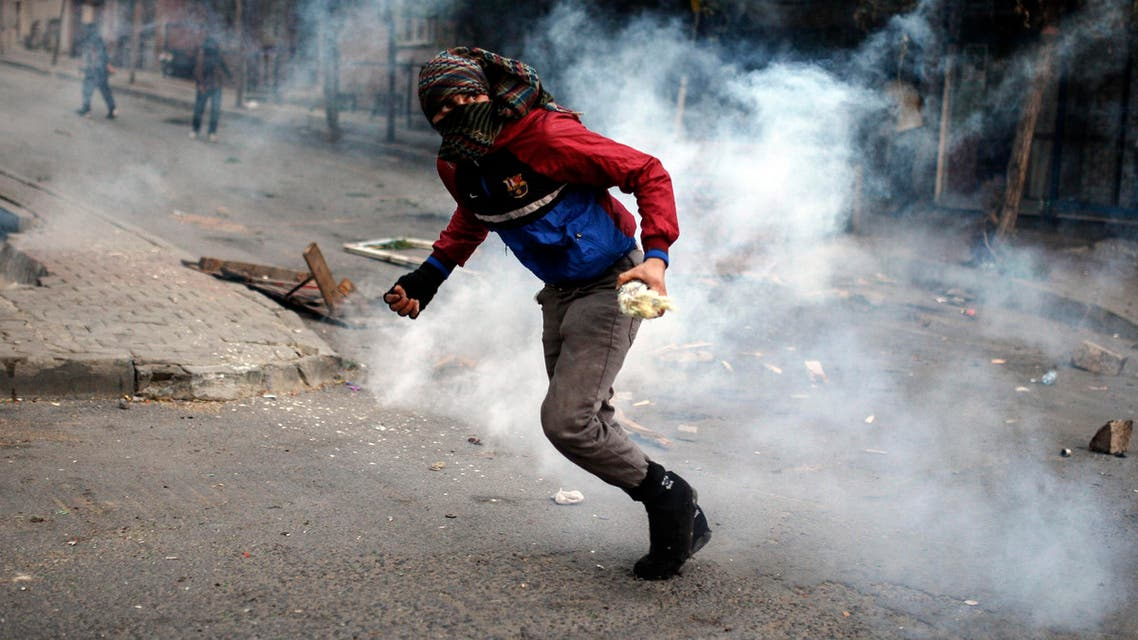 A masked leftist militant runs as they clash with security forces during a protest in Gazi district in Istanbul. (AP)