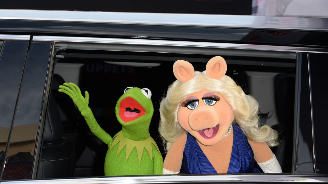 """In this March 11, 2014 file photo, Kermit the Frog and Miss Piggy arrive for the world premiere of Disney's """"Muppets Most Wanted,"""" at the El Capitan Theatre in Hollywood, California. A new piggy is in town, and this time her name is Denise. After Muppets star characters Kermit the Frog and Miss Piggy ended their relationship less than a month ago, both puppets have been given new love interests, according to People magazine. """"Kermit, who is still working with Miss Piggy on her late-night talk show Up Late with Miss Piggy - a situation that is being documented on the upcoming ABC series The Muppets - has been spotted around town numerous times with a head of marketing at ABC named Denise,"""" the magazine reported September 2, 2015. AFP PHOTO / ROBYN BECK / FILES"""