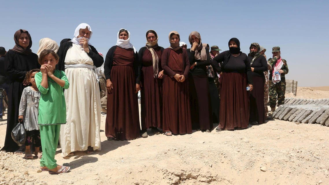 Yazidi women, relatives of Yazidis who were killed by militants of the Islamic State, stand near the coffins during a burial ceremony at Mazar Sharaf al-Din, north of Sinjar Mountain, August 13, 2015. (File: Reuters)