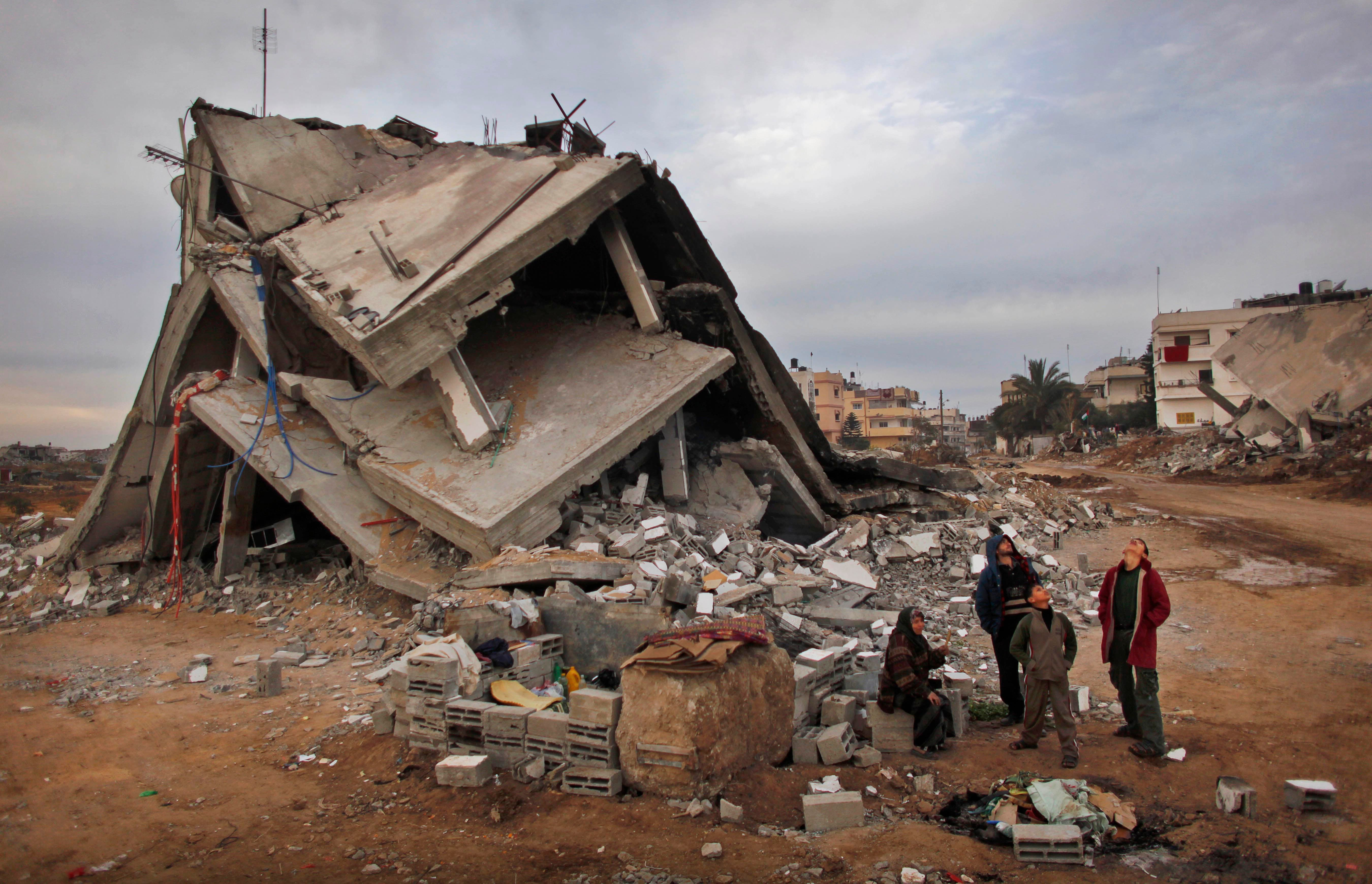 Palestinians look up at an Israeli air force unmanned drone as they stand in the rubble of their destroyed house in the area of east Jebaliya, in the northern Gaza Strip, that was devastated in the last Israeli military offensive, Wednesday, Jan. 28, 2009. (Reuters)