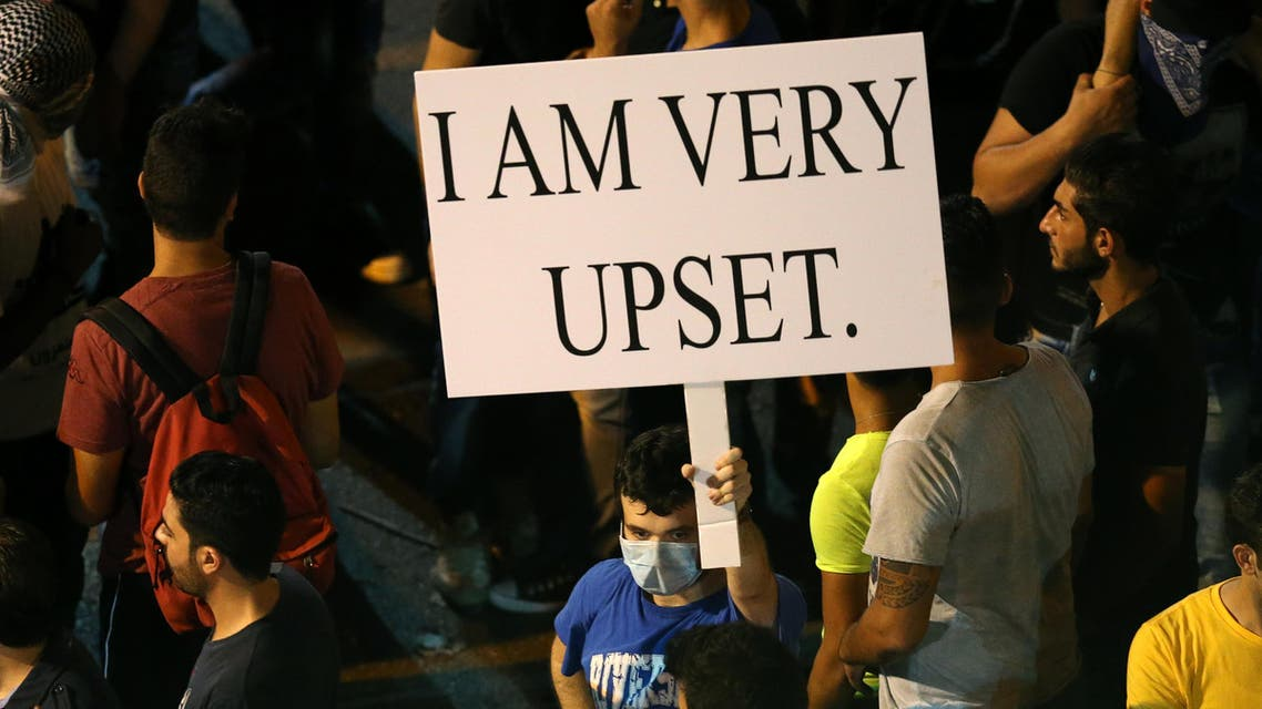 In this Saturday, Aug. 29, 2015 file photo, a Lebanese anti-government protester holds a placard during a demonstration against the on-going trash crisis and alleged government corruption, in Beirut, Lebanon. (AP Photo/Hussein Malla, File)